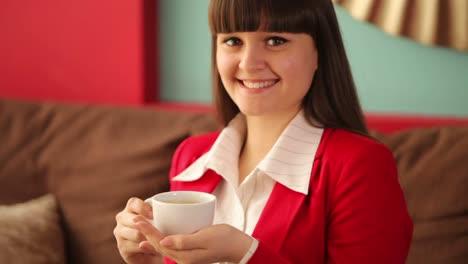 Mujer-Joven-Con-Una-Taza-De-Café-Sonriendo-A-La-Cámara