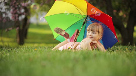 Children-Lying-With-Umbrella-And-Smiling