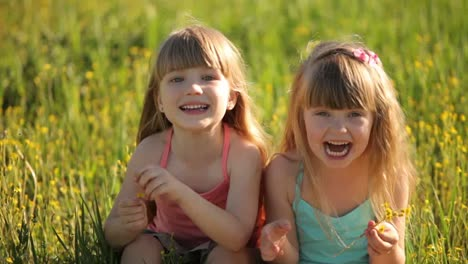 Children-Sitting-In-Field-And-Laughing
