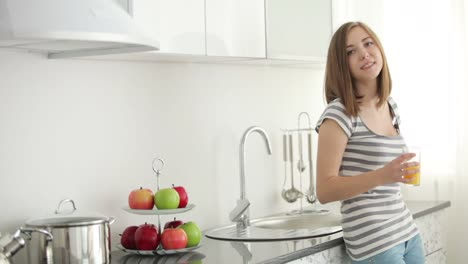 Cute-Girl-Drinking-Juice-In-The-Kitchen