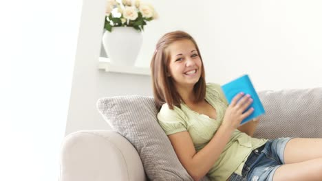 Cute-Girl-Sitting-On-Sofa-Reading-Book-And-Smiling-At-Camera