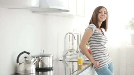 Cute-Girl-Standing-In-The-Kitchen-And-Straightens-Hair