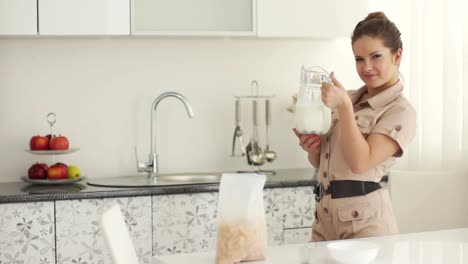Cute-Woman-Standing-In-Kitchen-And-Holding-Carafe-Of-Milk