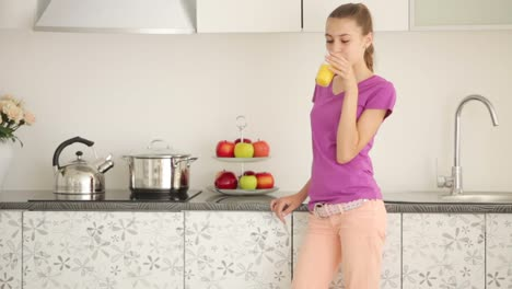 Girl-Drinking-Juice-In-The-Kitchen-And-Smiling-At-The-Camera