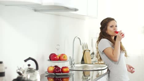 Girl-Is-Standing-In-Her-Kitchen-And-Drinking-Delicious-Juice