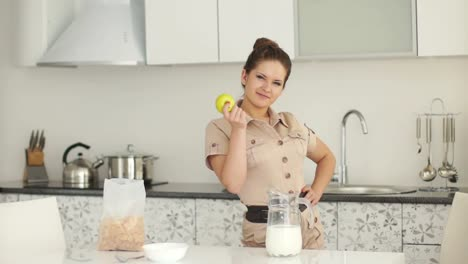 Girl-Is-Standing-In-The-Kitchen-And-Holding-An-Apple