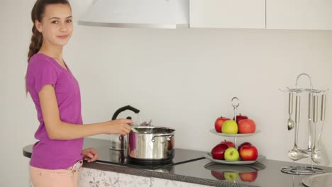 Girl-Is-Standing-In-The-Kitchen-And-Stir-The-Food-In-The-Pan