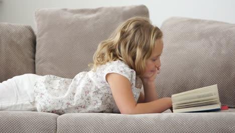 Niña-Acostada-En-El-Sofá-Y-Lee-Un-Buen-Libro