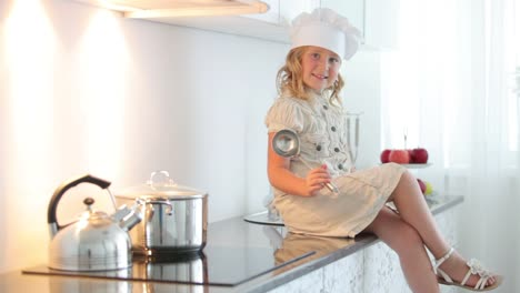 Girl-Sitting-On-The-Kitchen-Table-With-A-Ladle-And-Smiling-01