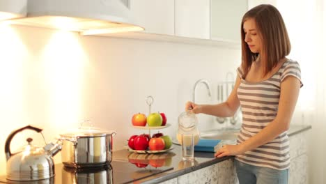 Girl-Standing-In-Kitchen-And-Finishes-Reading-Book-After-She-Pours-Milk-Into