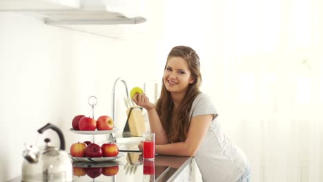 Girl-Standing-In-Kitchen-And-Holding-An-Apple