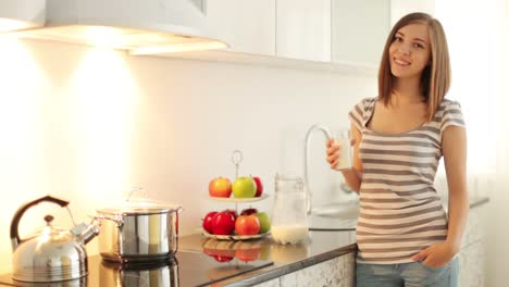 Girl-Standing-In-Kitchen-And-Holding-Glass-Of-Milk