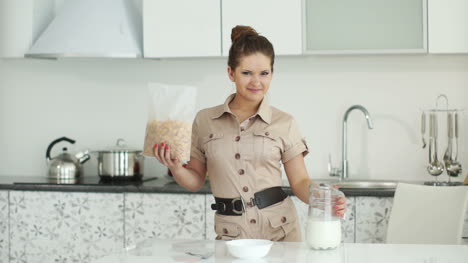 Girl-Standing-In-Kitchen-With-Corn-Flakes-And-Milk