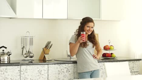 Girl-Standing-In-The-Kitchen-With-A-Glass-Of-Juice