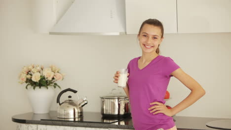 Girl-Standing-In-The-Kitchen-With-Glass-Of-Milk