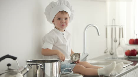 Little-Boy-Sitting-With-A-Ladle-And-Smiling