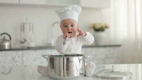 Little-Chef-Sitting-In-Front-Of-Pan-With-Spoon-And-Eating-Something
