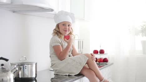 Little-Girl-Chef-Is-Sitting-At-The-Kitchen-Table-And-Eating-An-Apple