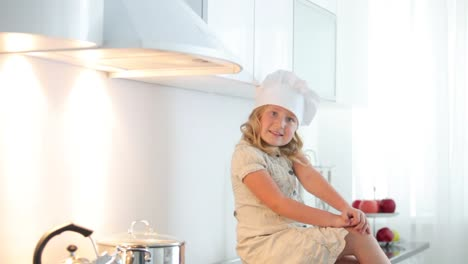 Little-Girl-Chef-Sitting-At-Kitchen-Table-And-Smiling