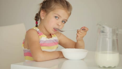 Little-Girl-Eating-Cereal-With-Milk-And-Smiling