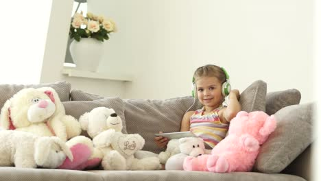 Little-Girl-Listening-To-Music-And-Looking-At-The-Camera-With-A-Smile