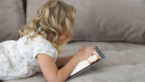 Niña-Acostada-En-El-Sofá-Y-Jugando-En-La-Tablet-Pc