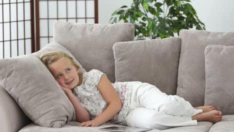 Niña-Descansando-En-Un-Sofá-Y-Sonriendo