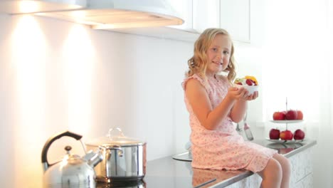 Little-Girl-Sitting-On-Table-And-Holding-Plate-Of-Fruit-Yoghurt