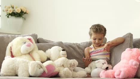 Little-Girl-Sitting-On-The-Couch-With-A-Tablet-PC-In-Toys