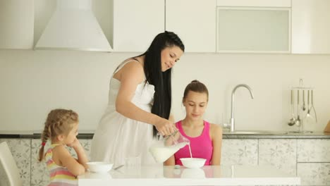Mother-pours-milk-in-corn-flakes-for-her-children