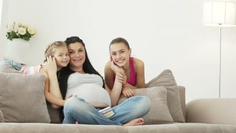 Pregnant-Girl-Kissing-Her-Daughters-And-Smiling