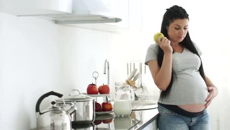 Mujer-Embarazada-Comiendo-Manzana-Y-Acariciando-La-Barriga