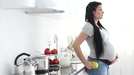 Pregnant-Woman-Is-In-The-Kitchen-And-Eating-An-Apple