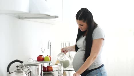 Pregnant-Woman-Pouring-Milk-Into-A-Glass