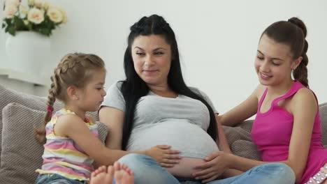 Mujer-Embarazada-Sentada-En-Un-Sofá-Y-Hablando-Con-Sus-Hijas