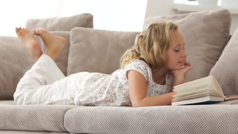 Sweet-Girl-Resting-On-The-Couch-And-Reading-A-Book