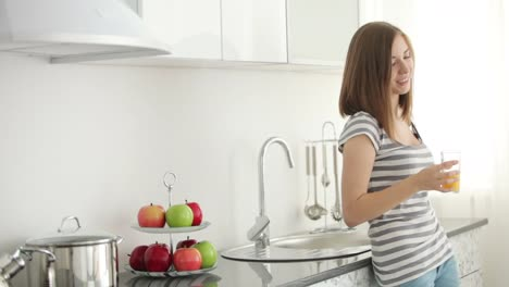 Teenager-Standing-In-Her-Kitchen-And-Drinking-Fresh-Juice