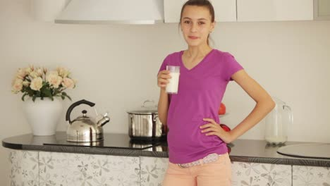 Teenager-Standing-In-Kitchen-And-Drinking-Milk