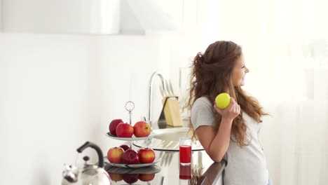 Teenager-Standing-In-Kitchen-With-Apple-And-Glass-Of-Juice