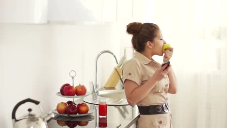 Teenager-Standing-In-Kitchen-With-Phone-And-Eating-An-Apple