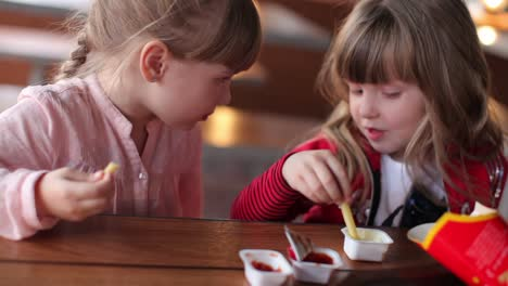Two-Girls-Are-Eating-French-Fries-In-Cafe