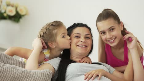 Two-Girls-Kissing-Their-Pregnant-Mother