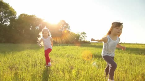 Two-Girls-Running-On-Grass-And-Smiling