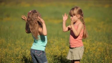 Two-Little-Girls-Clap-Their-Hands-In-Flowers