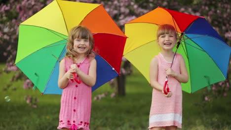 Zwei-Kleine-Mädchen-Mit-Regenschirmen-Lachen