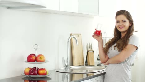 Woman-Drinking-Juice-And-Smiling-At-Camera
