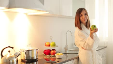 Woman-In-Bathrobe-Holding-An-Apple-And-Smiling