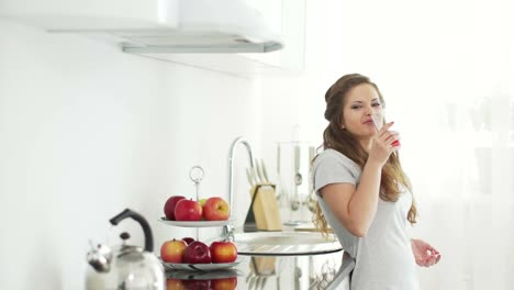 Woman-Standing-In-Kitchen-And-Drinking-Juice