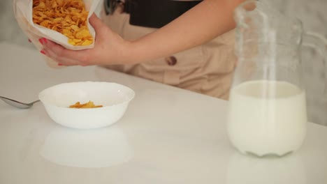 Woman-Standing-In-Kitchen-And-Fills-The-Bowl-Of-Cornflakes-Closeup