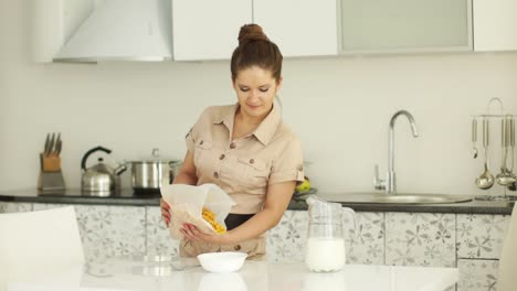 Woman-Standing-In-Kitchen-And-Fills-The-Bowl-Of-Cornflakes
